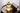 Braunes Holztablett mit kleiner Ölflasche mit hellbraunem Öl und halbierter Kokosnuss auf dunklem Tisch