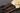 Nahaufnahme einiger dunkler Vanilleschoten mit großer cremefarbener Bluete auf dunklem Untergrund