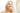 Blonde lächelnde Frau steht mit einem Cremetiegel in der Hand vor dem Spiegel und cremt sich das Gesicht ein