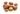 Mehrere ungeschälte Argannüsse  und eine offene Nuss mit Öl auf weißem Hintergrund