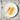 Weißer Porzellanteller mit einer Honigwabe und einem Honiglöffel auf Holztisch
